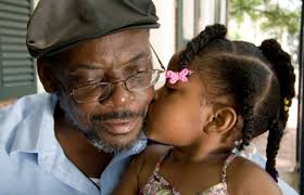 Girl kissing her grandpa on the cheek